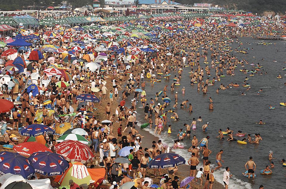 ) Субботним днем тысячи людей ютятся на пляже, во время летнего зноя в китайском городе Далянь, провинция Ляонин. (Xinhua News Agency/Associated Press)