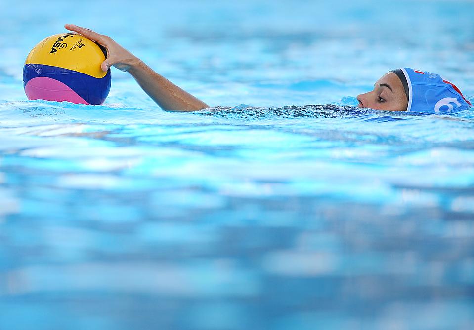 ) Итальянка Арианна Гариботти хватает мяч во время ватерпольного матча против Узбекистана на Чемпионате по водным видам спорта FINA в Риме. Италия выиграла эту игру со счетом 20-3. (Alberto Pizzoli/Agence France-Presse/Getty Images)
