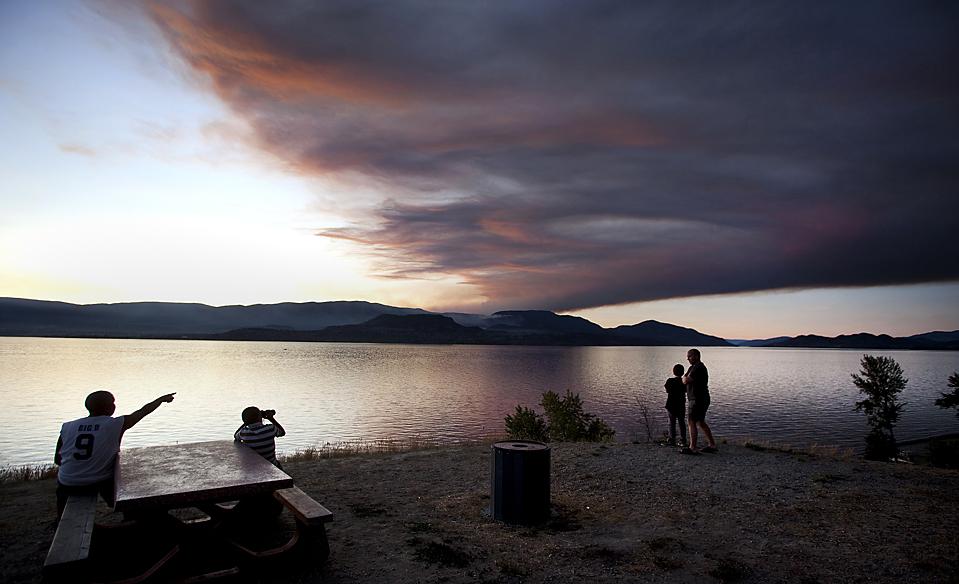 ) Люди смотрят на дым от лесных пожаров недалеко от озера в Оканаган Келоуна, в Британской Колумбии в Канаде. Пожары вынудили тысячи людей покинуть свои дома в западной части Канады. Сообщений о пострадавших и раненых не поступало, но по крайней мере, три дома были разрушены. (Andy Clark/Reuters)