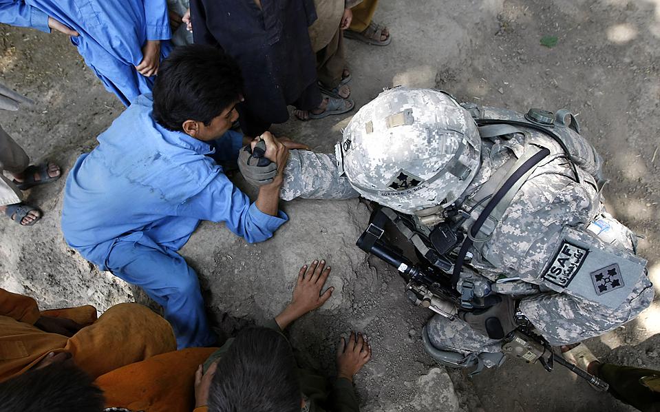 6) Военнослужащий армии США, 2-12 пехотных войск, 4 бригады, борется на руках с местными жителями во время патрулирования деревни Колак в афганской провинции Кунар. (Tim Wimborne/Reuters)