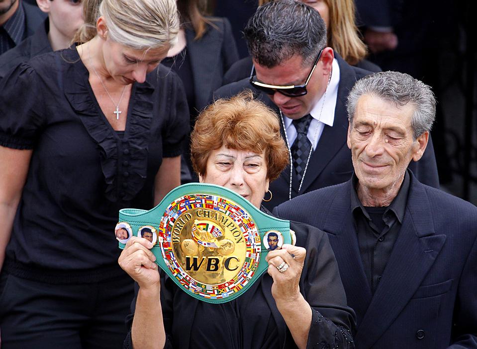 14) Ида Гатти, мать бывшего чемпиона мира - боксера Артуро Гатти, 37 лет, держит пояс Всемирного совета бокса, во время его похорон в Монреале понедельник. Жена Гатти жены, Аманда Родригиш, сейчас проходит в качестве главного подозреваемого в убийстве, произошедшем 11 июля. Ее муж был задушен во сне ручкой сумки. (Shaun Best/Reuters)
