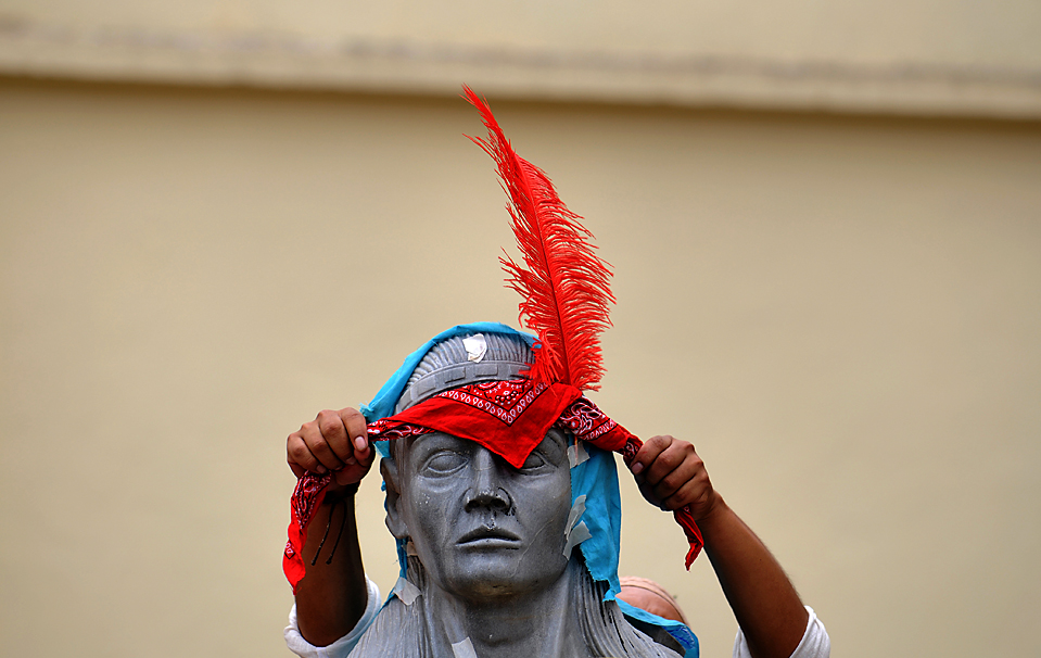 15) Сторонник изгнанного президента Гондураса Мануэля Селайи повязывает перо на памятник туземному лидеру во время демонстрации протеста в столице Гондураса Тегусигальпе. Переговоры по восстановлению спокойствия в стране потерпели неудачу в воскресенье в Коста-Рике. (Jose Cabezas/Agence France-Presse/Getty Images)