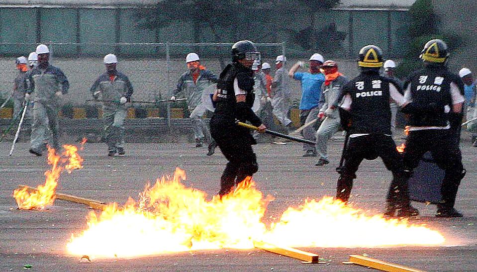 16) Уволенные рабочие завода «Ssangyong Motor» бросают бутылки с зажигательной смесью в полицию по охране общественного порядка на заводе компании в южнокорейском городе Пхёнтхэк (Pyeongtaek). Вертолеты распыляли на рабочих слезоточивый газ. Некоторые из рабочих уже два месяца участвуют в забастовке, в ходе которой уволенные работники захватили и удерживаю завод компании. (Kim Dong-kyu/Yonhap via Associated Press)