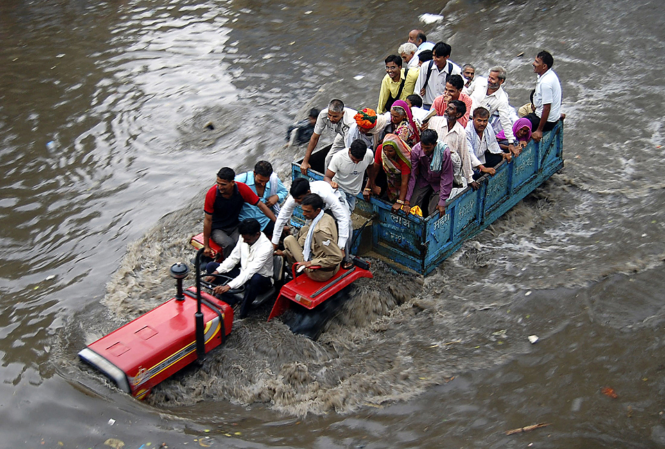 1) Жители индийского города Матхура едут на тракторе с прицепом по улице затопленной проливными дождями. (K.K. Arora/Reuters)
