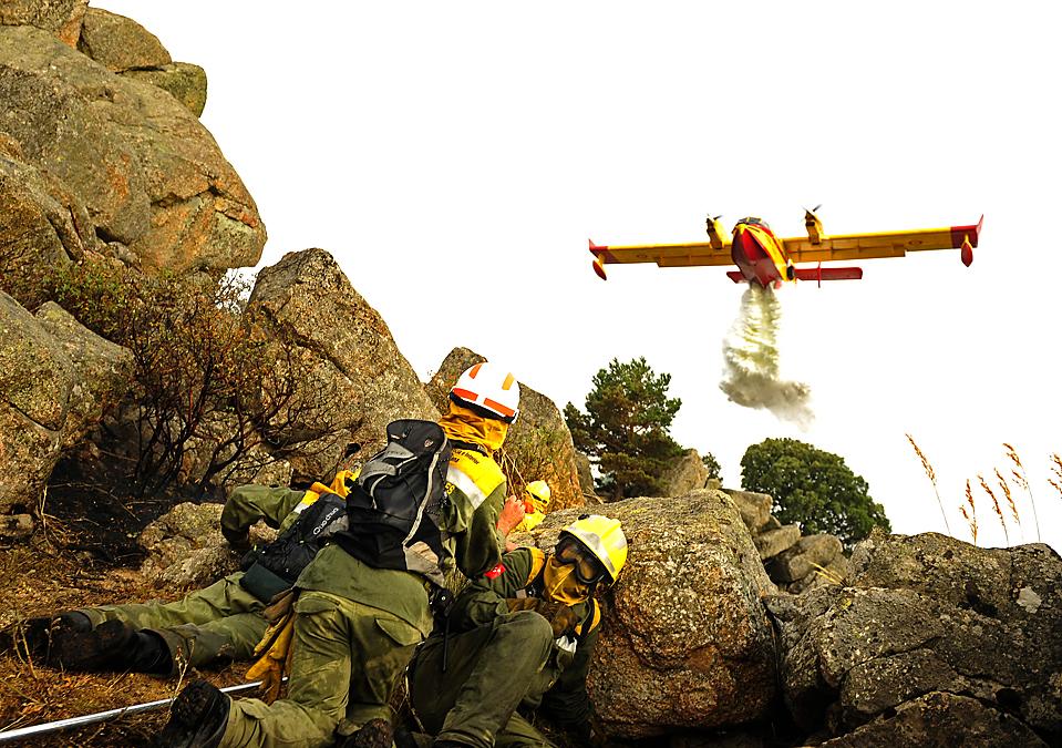 2) Пожарные прячутся в укрытии, а на фоне самолет пролетает над лесным пожаром вблизи испанского города Колладо Медианно. Во время борьбы с огнем четверо пожарных погибли, а двое получили серьезные ранения. (Pedro Armestre/Agence France-Presse/Getty Images )
