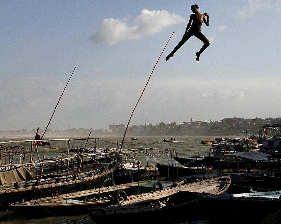 3) Мальчик прыгает с набережной в воды реки Ганга в индийском городе Варанаси. (Jayanta Shaw/Reuters)