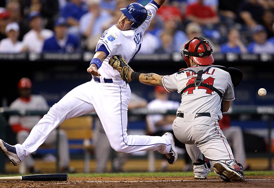 4) Джон Бак игрок команды «Kansas City Royals'» пробегает мимо кетчера Майка Наполи из команды «Los Angeles Angels». (Charlie Riedel/Associated Press)