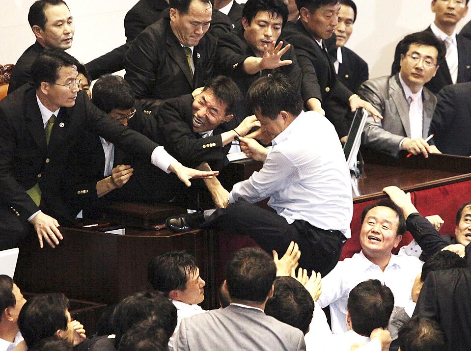 5) Заседание чиновников в здании Национальных собраний Республики Корея в Сеуле закончилось массовой потасовкой. Депутаты спорили по поводу законопроекта о средствах массовой информации. По меньшей мере один человек был отправлен в больницу. (Ahn Young-joon/Associated Press)