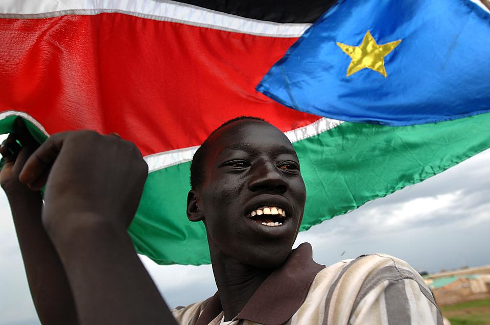 8) Житель области Abyei марширует с флагом Южного Судана после того, как международный арбитраж присудил суданскому правительству контролировать практически все крупные нефтяные запасы в этом спорном регионе. Оппозиционные боевики заявили, что принимают это решение. (Tim McKulka/Agence France-Presse/Getty Images)