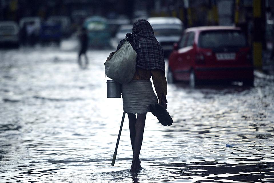 10) Мужчина идет с сандалиями в руках по затопленной дороге после ливневых дождей в индийском штате Джамму. (Channi Anand/Associated Press)