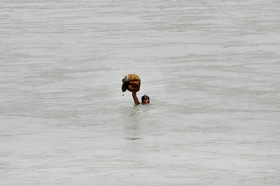 11) Мальчик со свертком одежды переплывает реку в Джелалабаде в афганской провинции Нангархар. (Рахмат Гюля/Associated Press)