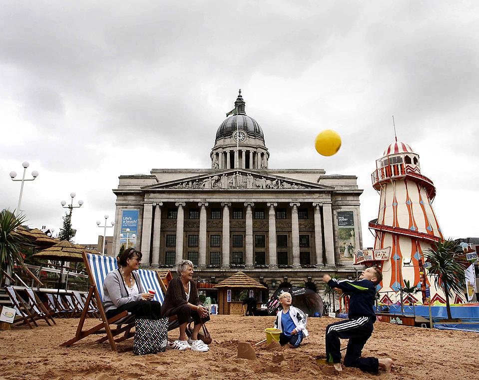 12) Дети играют на самом большом в Великобритании городском пляже в английском городе Ноттингем. Сюда доставили около 300 тонн песка, чтобы превратить бывшую рыночную площадь в морскую игровую площадку. (Даррен Staples/Reuters)