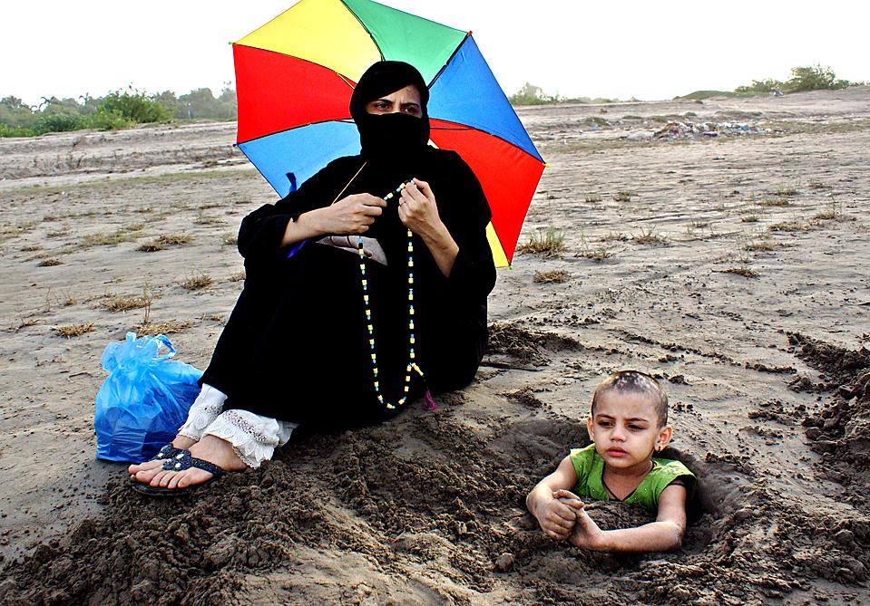 13) Пакистанская женщина сидит на берегу реки Инд со своим ребенком, у которого парализована половина тела во время солнечного затмения в Хайдарабаде 22 июля 2009. 22 июля пакистанские родители закапывали своих парализованных детей до шеи в илистое русло реки, полагая, что полное затмение солнца излечит их. (YOUSUF NAGORI/AFP/Getty Images)