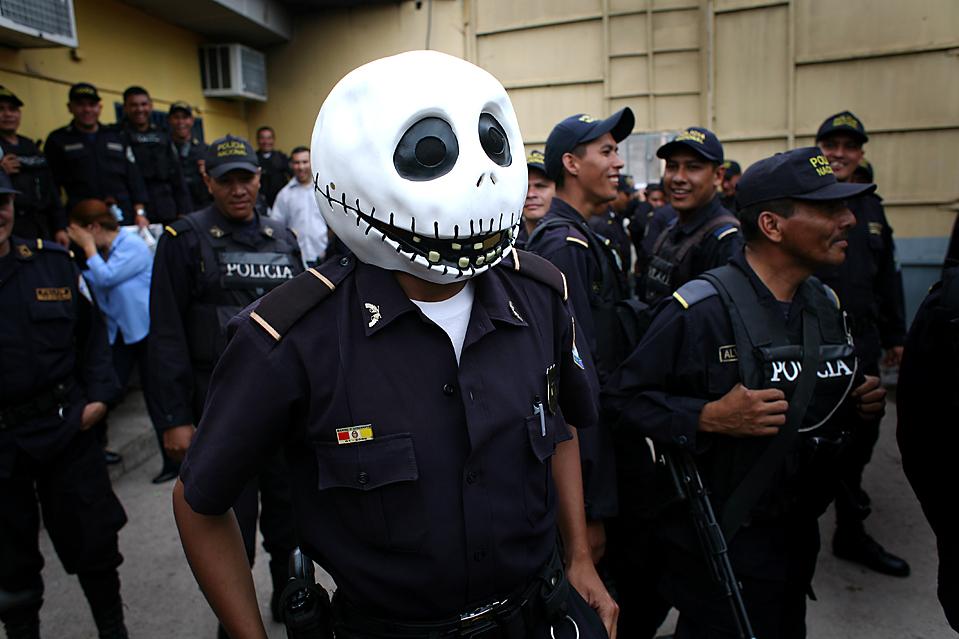 2) Полицейский в маске стоит со своими коллегами у полицейского участка в Тегусигальпе, Гондурас. Сторонники свергнутого президента Мануэля Селайи в прошлый четверг объявили двухдневную всеобщую забастовку, требуя его возвращения. (Rodrigo Abd/Associated Press)