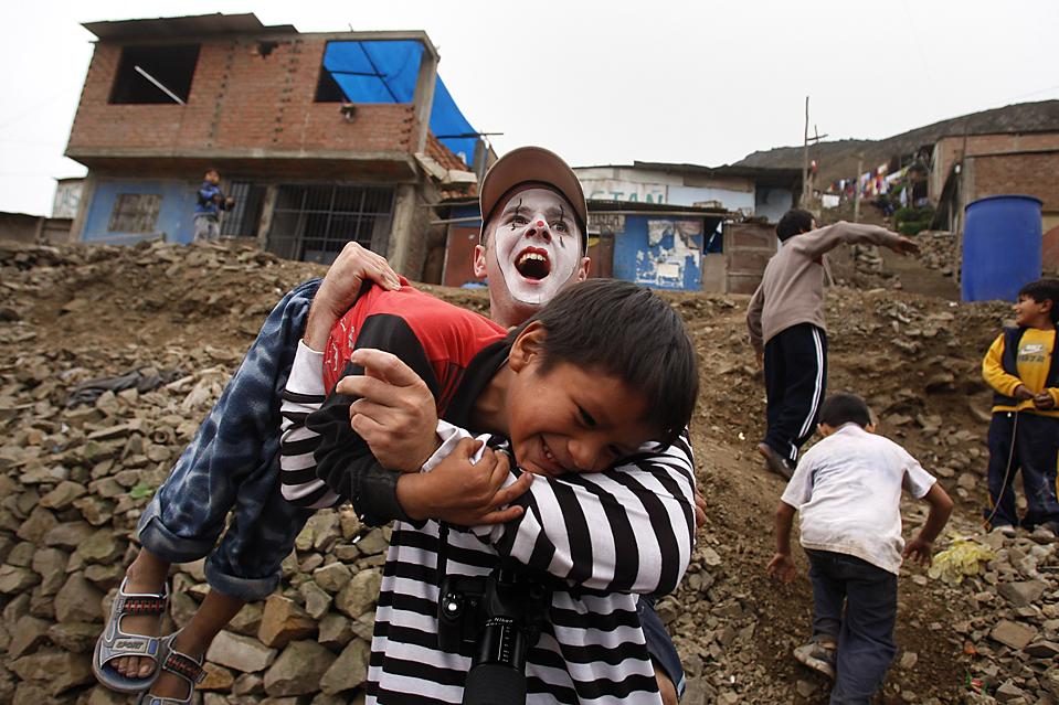 7) Доброволец из группы «Заботливые клоуны» играет с детьми в трущобах перуанского города Лимы. (Pilar Olivares/Reuters)