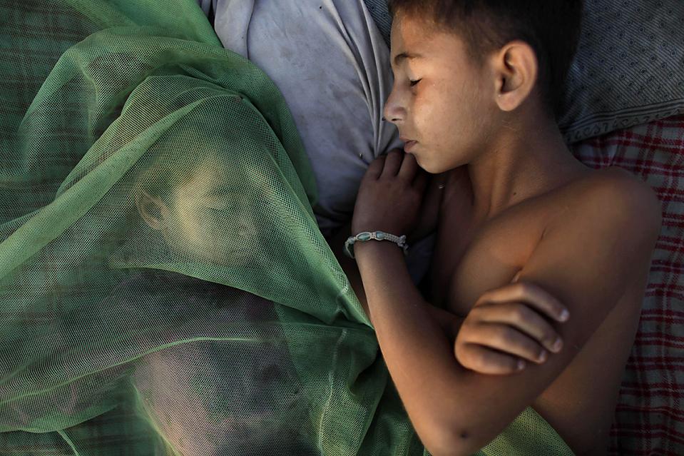 8) Дети спят под противомоскитными сетками на окраине Исламабада, Пакистан. (Alexandre Meneghini/Associated Press)