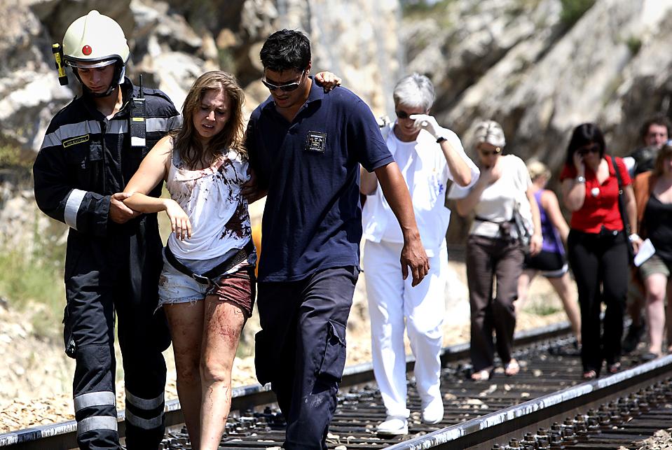 10) Спасатели и пассажиры на месте, где рядом с населенным пунктом Рудине в пятницу с рельсов сошел поезд. По меньшей мере, шесть человек погибли, 50 получили ранения. (Mario Strmotic/Associated Press)