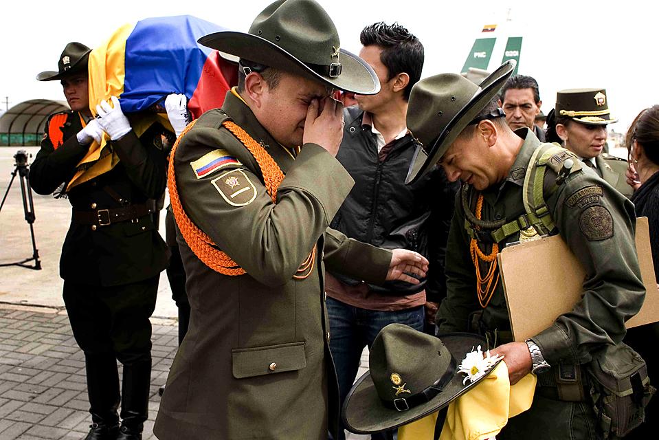 11) Полицейские оплакивают своего товарища Джимми Теллез в колумбийском городе Богота. Как сообщают официальные источники, Теллез был убит в прошлую среду в результате взрыва бомбы на севере Колумбии. (William Fernando Martinez/Associated Press)
