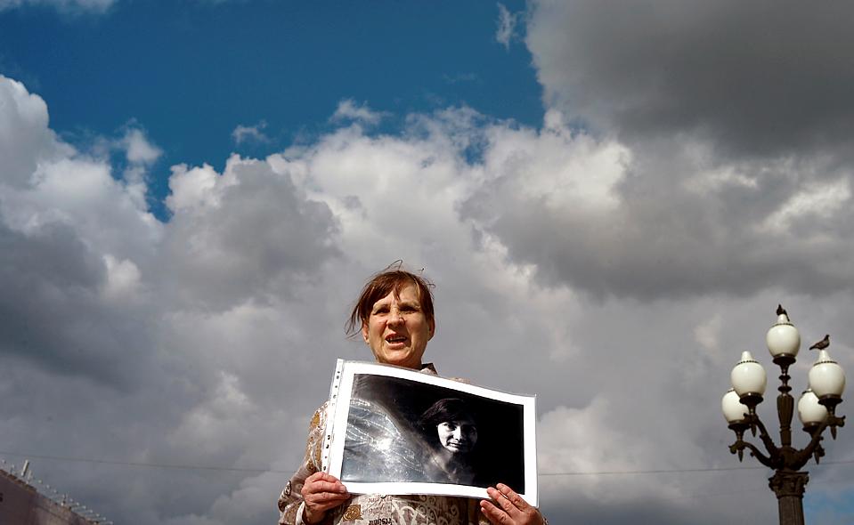 12) Женщина держит портрет правозащитницы Натальи Эстемировой на митинге в Москве в прошлый четверг. Г-жа Эстемирова была убита выстрелом в голову 15 июля на пороге своего дома. Президент Чечни Рамзан Кадыров отрицает факт заказного убийства. (Alexander Zemlianichenko/Associated Press)