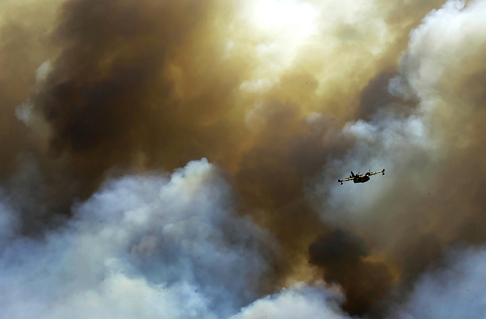16) Самолет пожарной службы пролетает через дым лесного пожара недалеко от греческого города Фивы. Пожар сдерживали шесть самолетов и два вертолета. (Petros Giannakouris/Associated Press)
