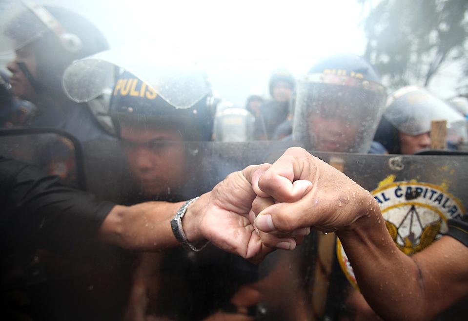 2) Демонстранты, сдерживаемые полицией по охране общественного порядка, пытались попасть на Филиппинский конгресс в Маниле. Президент Глория Макапагал Арройо, находящийся на своем посту уже 8,5 лет торжественно пообещала в понедельник не продлевать свои полномочия. (Bullit Marquez/Associated Press)