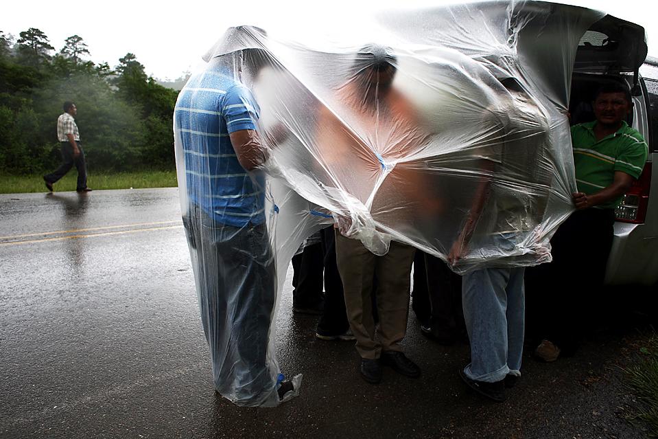 8) Люди укрываются от дождя, стоя у военного поста в городе Jacagalpa, Гондурас. В пятницу свергнутый президент Гондураса Мануэль Селайя пообещал вернуть свой пост. Незадолго до этого он вернулся в Никарагуа, заявив, что риск кровопролития слишком велик. (Rodrigo Abd/Associated Press)