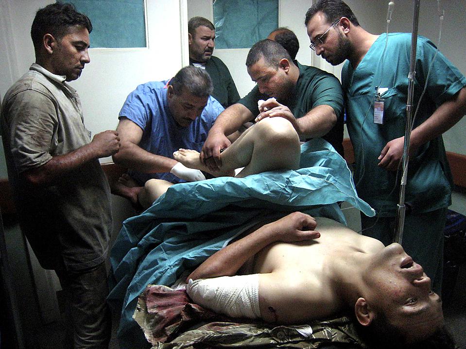 9) Врачи осматривают человека, который пострадал от взрыва бомбы заложенной под его автомобиль в Киркуке, Ирак. Высокопоставленный офицер иракской армии, родовой глава суннитов и еще двое человек были убиты в понедельник. (Emad Matti/Associated Press)