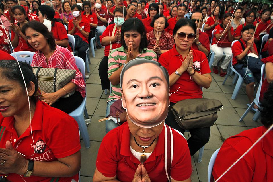 12) Сторонники бывшего премьер министра Таиланда Таксина Чинавата собрались на церемонию празднования его дня рождения недалеко от Бангкока. Таксин бежал из страны из-за угрозы попасть в тюрьму по обвинению в коррупции. (David Longstreath/Associated Press)
