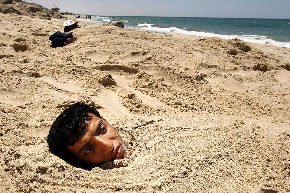 13) Палестинцы закапываются в песок на пляже в Хан Юнис в Секторе Газа. Такие песочные процедуры традиционно применяются для лечения кожных и мышечных заболеваний. (Ibraheem Abu Mustafa/Reuters)