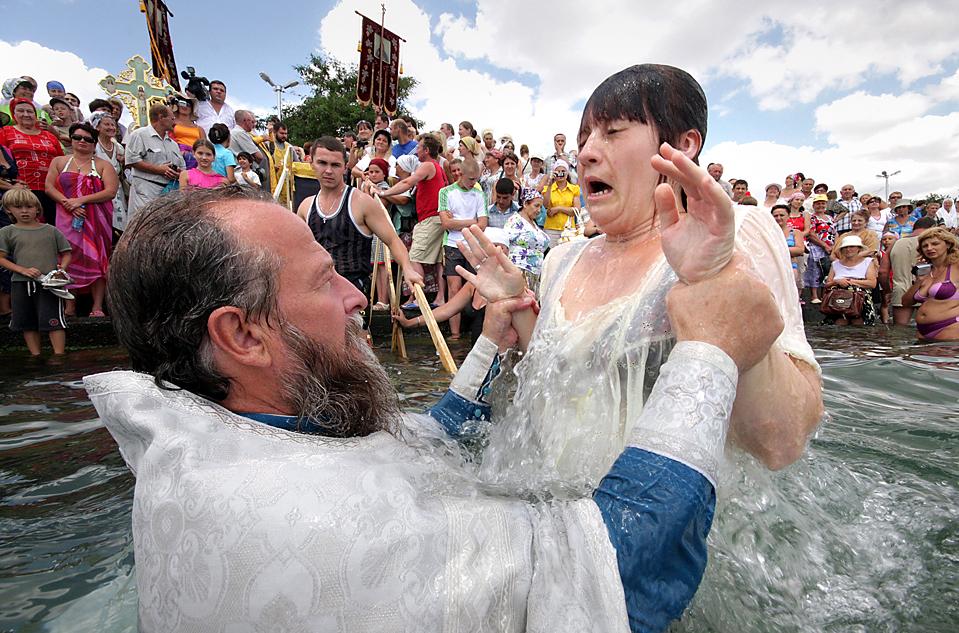 2) Православный священник крестит женщину во время празднования крещения Киевской Руси в Севастополе. (Reuters)