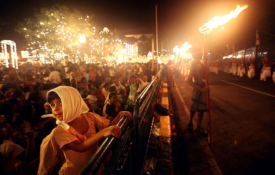 3) Шриланкийцы на ежегодном буддийском фестивале Эсала Перахера в Канди, Шри-Ланка. Тысячи людей выстроились вдоль улицы, что бы увидеть зуб Будды. Зуб хранится в храме, который был частично разрушен от террористического акта 1998-го года. (Mario Tama/Getty Images)