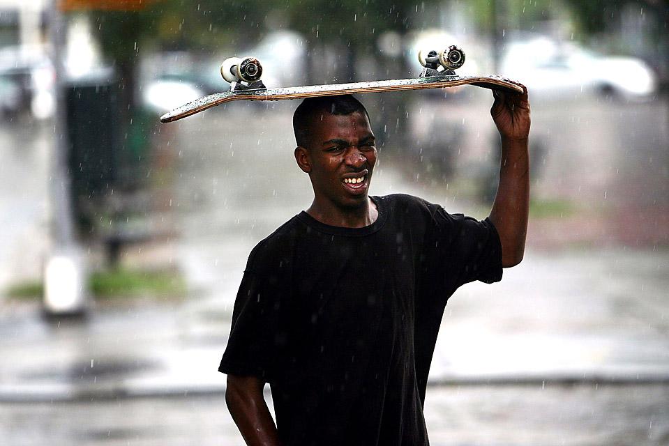 7) Подросток укрывается от дождя под скейтбордом во время полуденной грозы в Нью-Йорке. В воскресенье в Ньюарке, штат Нью-Джерси молнией убило одного и ранило трех человек, укрывавшихся от дождя под деревом. (Spencer Platt/Getty Images)