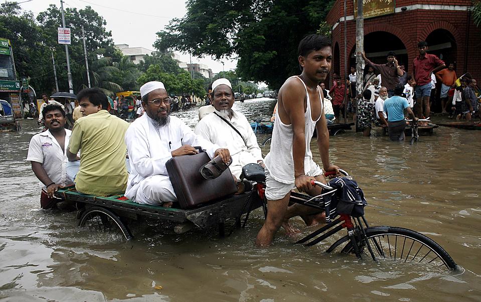 8) Велорикша везет пассажиров по затопленной улице Дакке, Бангладеш. Сильнейшие за последние 53 года проливные дожди затопили столицу страны, в результате чего были повреждены линии электропередач, шесть человек, в том числе и двое детей, погибли. Тысячи людей остаются в затопленных домах. (Andrew Biraj/Reuters)