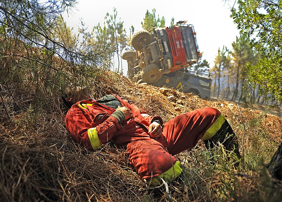 9) Военнослужащий испанской армии лежит на земле после автомобильной аварии. Дорожное происшествие произошло во время тушения военными лесного пожара в Вегас-де-Кориа, Испания. (Pedro Armestre/Agence France-Presse/Getty Images)