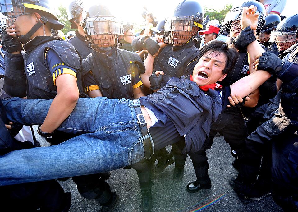 1) Полиция задерживает одного из участников митинга, который провели в поддержку бастующих работников автомобильного завода Ssangyong Motor Co в южно-корейском городе Пхёнтхэк, Южная Корея. Полицейские применили слезоточивый газ и задержали более 20 человек. Митинг был проведен после того, как кредиторы и поставщики приняли решение о ликвидации компании в случае, если рабочие не прекратят забастовку к концу этого месяца. (Jung Yeon-je/Agence France-Presse/Getty Images)