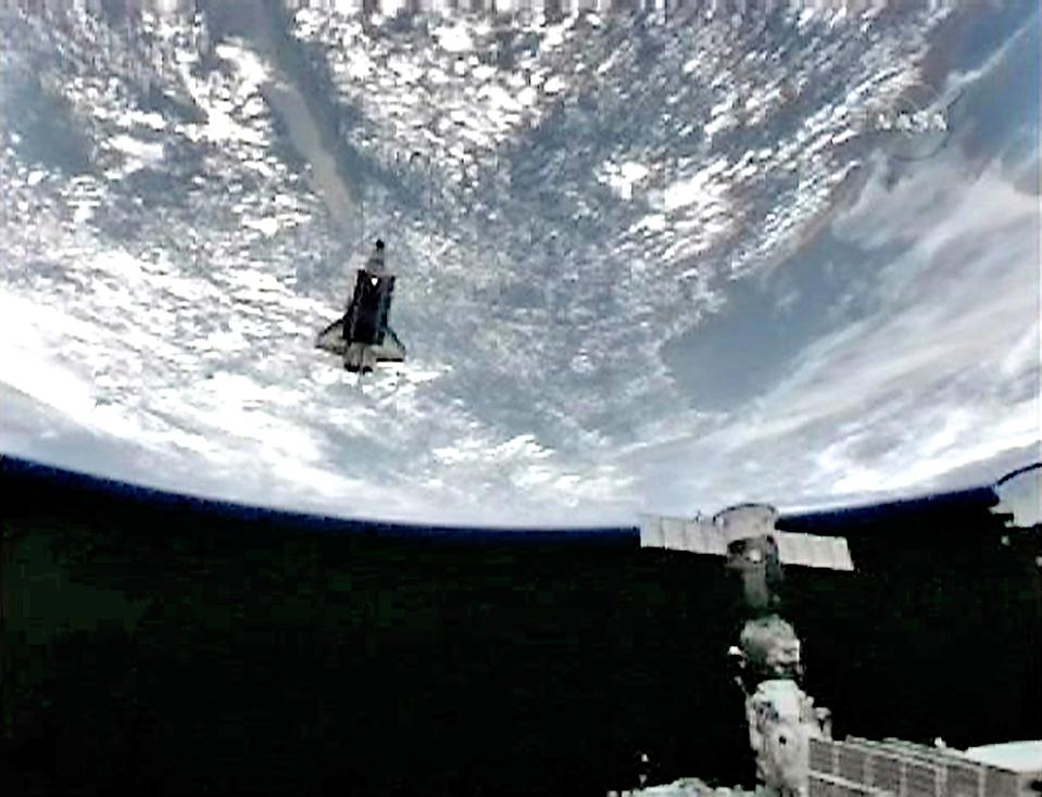 4) Шаттал «Endeavour» совершает облет вокруг МКС. Проведя тщательный осмотр с помощью камер и лазера, космонавты не обнаружили каких-либо видимых повреждений в тепловой защите корабля. (NASA TV/Reuters)