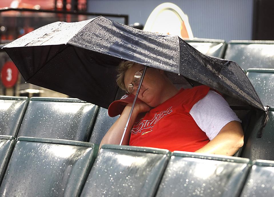 8) Болельщик команды «St. Louis Cardinals» под дождем на бейсбольном матче против «Los Angeles Dodgers» в Сент-Луисе. Кардиналы выиграли со счетом 10-0. (Tom Gannam/Associated Press)