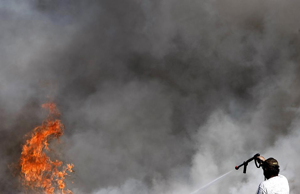 15) Работник свалки тушит пожар в пригороде Аспропиргоса к западу от Афин. (Yiorgos Karahalis/Reuters)