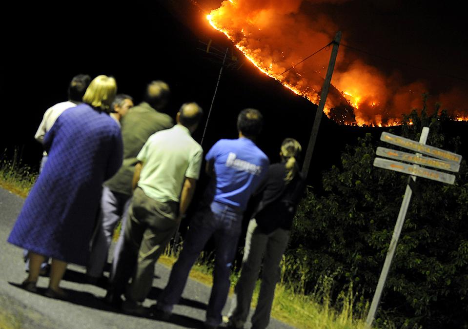 1) Жители наблюдают за лесным пожаром недалеко от испанского города Авила. Власти сообщают, что водитель бульдозера, участвующий в борьбе с огнем, и еще один человек погибли во время пожара во вторник. (Pierrephilippe Marcou/AFP/Getty Images)