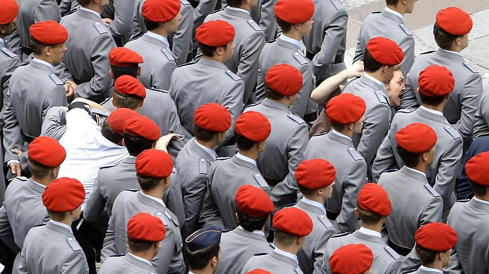 3) Сотрудник полиции, внизу слева, преследует участника акции протеста, вверху справа, который пробирается через толпу солдат стоящих навытяжку во время церемонии принятия присяги у здания муниципалитета Мюнхена.  В тот день около 500 человек были приведены к присяге. (Michaela Rehle/Reuters)