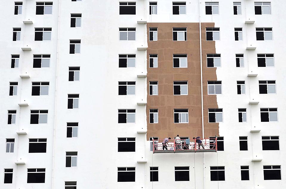 5) Рабочие красят фасад жилого дома в китайском городе Сянфань, Хубэй, четверг. Китай в скором времени разрешит запуск инвестиционных фондов недвижимости на межбанковском рынке, что даст девелоперам больше вариантов выхода из кризиса и расширения каналов для китайских инвесторов. (Reuters)