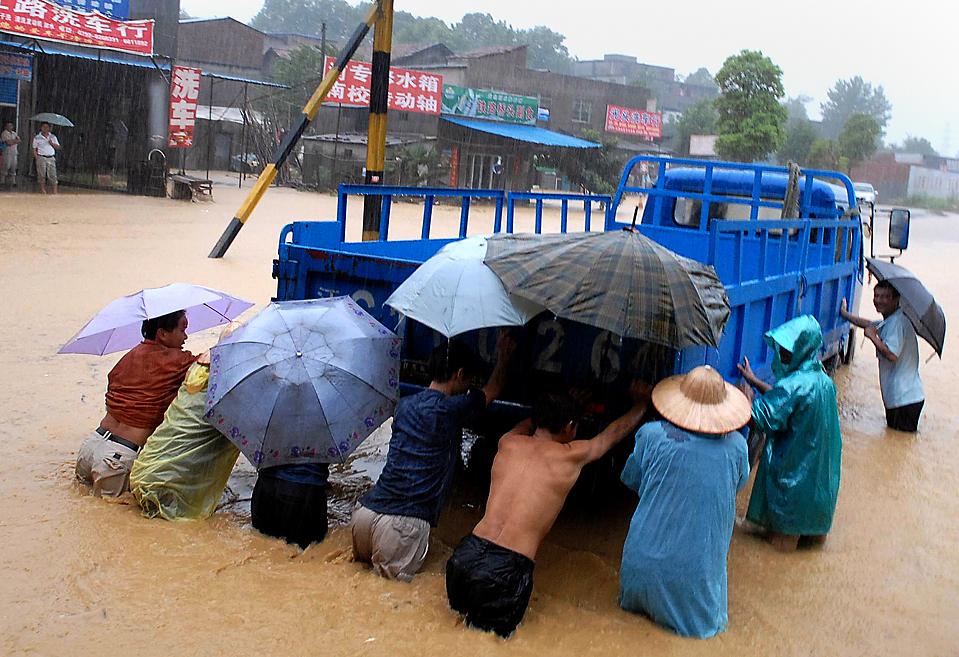 6) Жители толкают грузовик, который застрял в паводковых водах на одной из улиц в Джиуииан, в китайской провинции Цзянси. Как сообщили в четверг государственные средства массовой информации, с начала июня в южных и центральных районах Китая из-за проливных дождей и оползней погибли, по меньшей мере, 66 человек и еще 66 считаются пропавшими без вести. (Agence France-Presse/Getty Images)