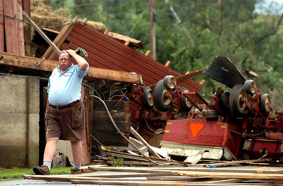 14) Дэвид Феннер на фоне обломков и перевернутых машин после торнадо в долине Черри Велли, штат Пенсильвания. (David Kidwell/Pocono Record via Associated Press)