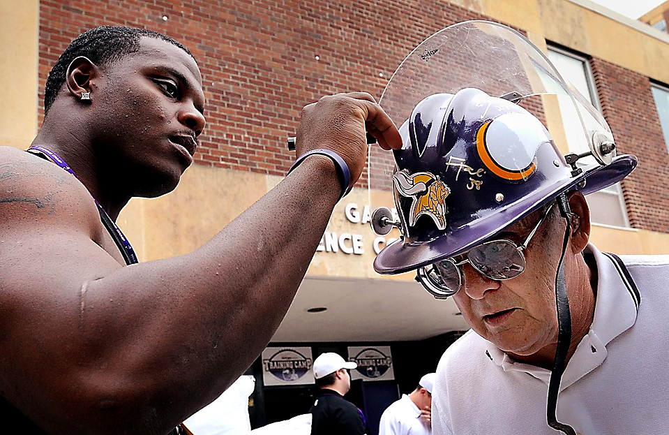 15) Игрок команды по американскому футболу «Minnesota Vikings» подписывает шлем болельщика Милта Торрати в кампусе университета штата Миннесоты в Манкато. (John Cross/Mankato Free Press via Associated Press)
