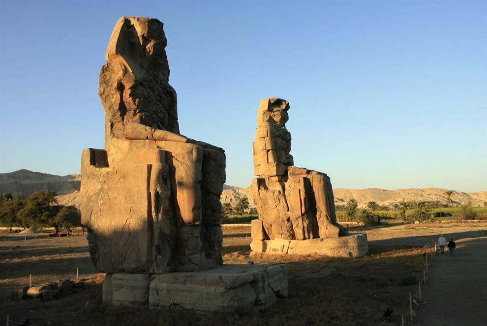 16) Туристы осматривают Колоссы Мемнона – 2 огромные каменные статуи фараона Имхотепа III. Статуи-близнецы расположены в Фиванском некрополе на противоположном от Луксора берегу Нила. (Khaled Desouki/AFP - Getty Images)