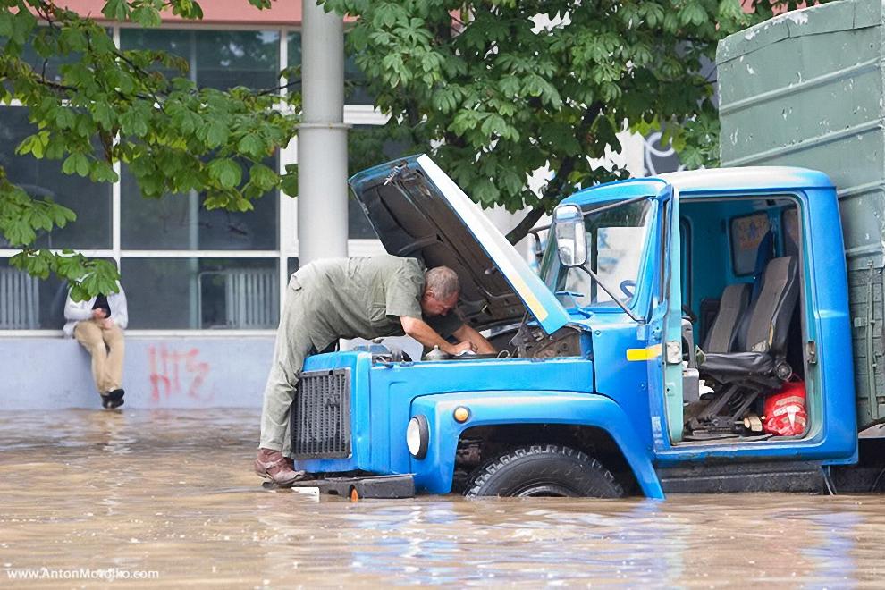 15) Возле торгового дома «Паркинг», на улице Куйбышева, автомобили застыли, погрузившись под воду по самые фары.