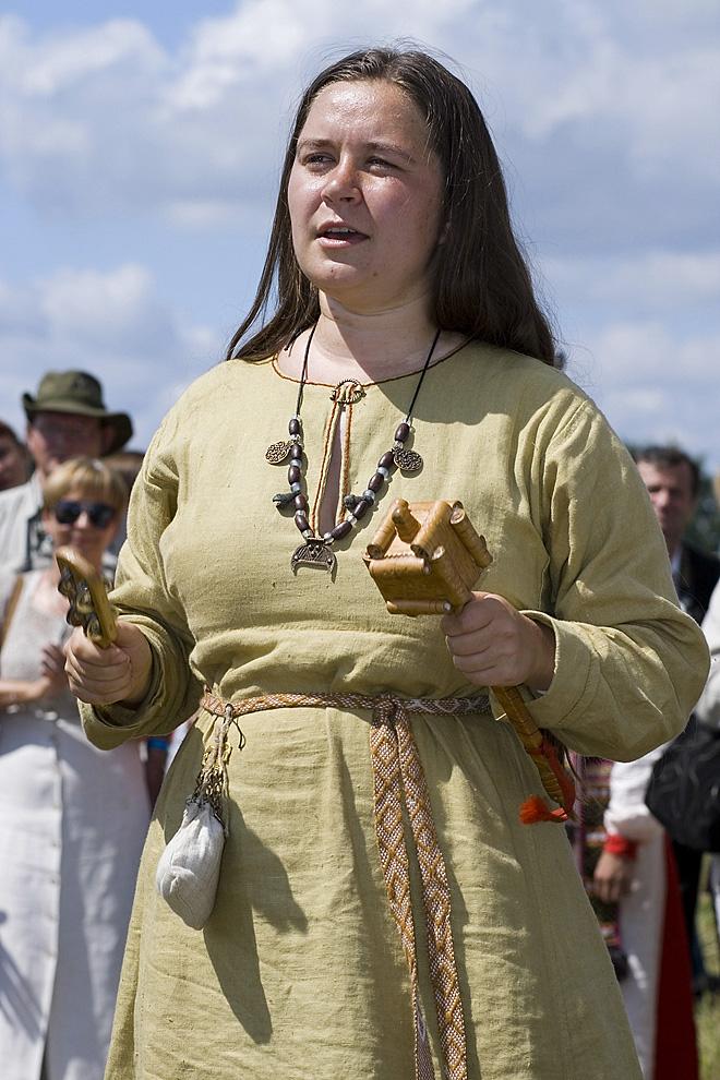 Женщина в средневековом костюме с трещотками