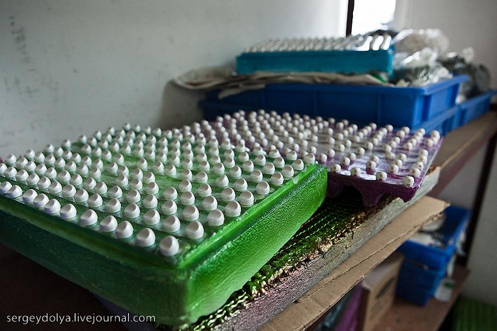 Мелкие наушники выкладывают на специальные подносы.