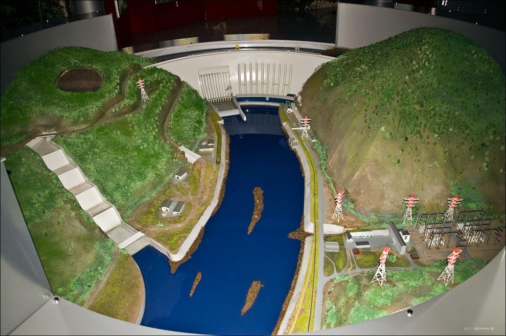 15) Модель комплекса сооружений СШГЭС. По центру - арочно-гравитационная плотина ГЭС, с машинным залом и устройством водосброса. Правее и ниже - ОРУ (открытые распределительные устройства), расположенные в небольшом ущелье, от которых электроэнергия идет по ЛЭП к потребителям. Левее - строящийся дополнительный береговой водосброс.