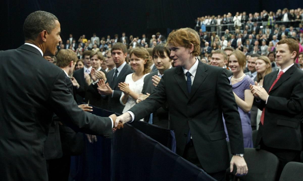 2) Барак Обама приветствует студентов во время посещения Новой Экономической Школы Москвы 7 июля. Речь Барака Обамы широко освящалась по российскому телевиденью. (Jim Young/Reuters)